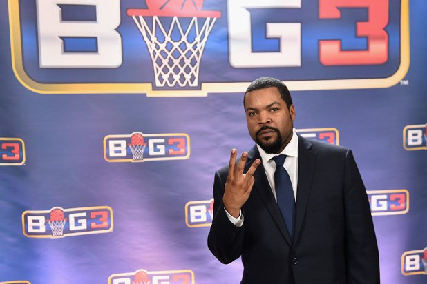 Big3 Founder, Ice Cube, posing with Big3 logo in background.